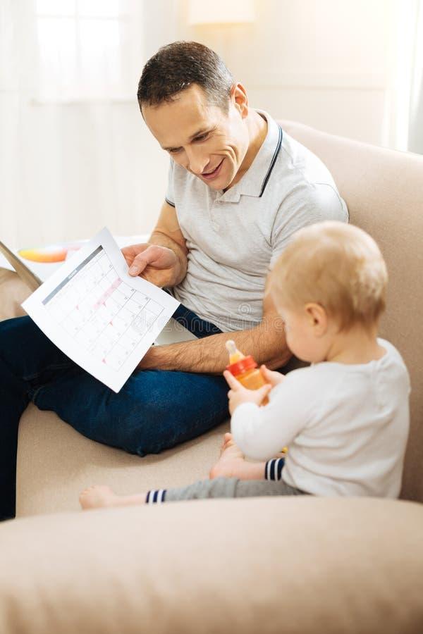 Pai emocional esperto que mostra seu gráfico a uma criança pequena ocupada foto de stock