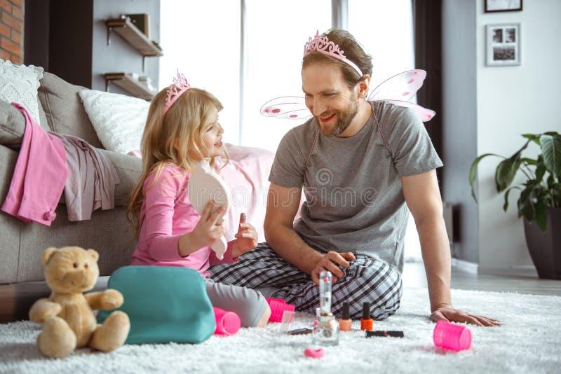 Pai entusiasmado e filha que jogam com cosméticos junto imagem de stock