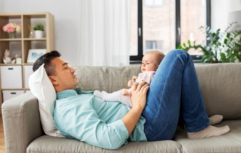 Pai envelhecido médio com o bebê que encontra-se no sofá em casa imagens de stock