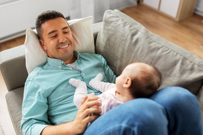 Pai envelhecido médio com o bebê que encontra-se no sofá em casa imagens de stock royalty free