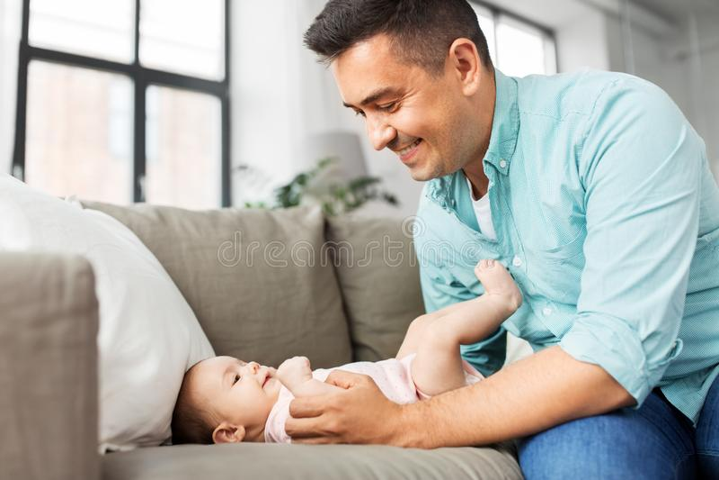 Pai envelhecido médio que joga com bebê em casa fotografia de stock royalty free