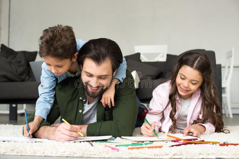 pai feliz com as crianças bonitos que encontram-se no tapete e que tiram com colorido fotos de stock royalty free