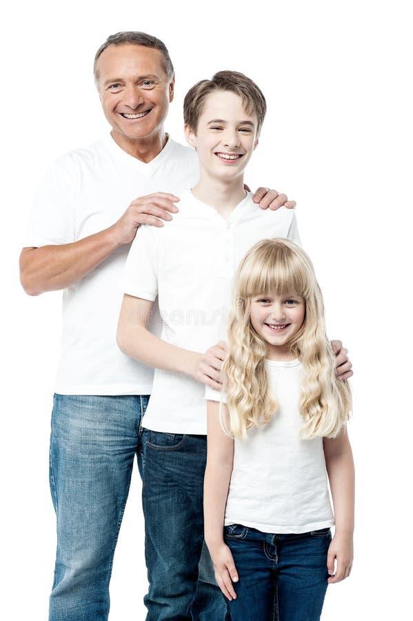 Pai feliz com as crianças que estão na fileira fotografia de stock royalty free