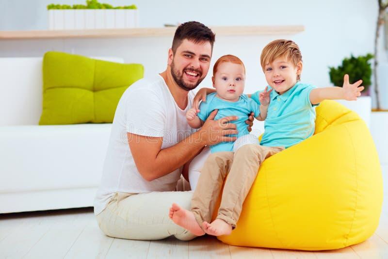 Pai feliz com de seis meses e seis anos de filhos idosos, em casa imagens de stock royalty free
