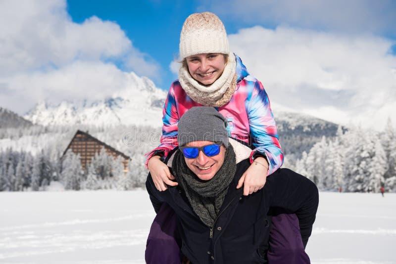 Pai feliz com a filha que aprecia férias do inverno sobre o fundo das montanhas imagens de stock