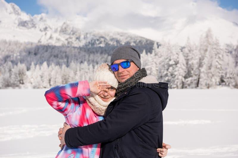 Pai feliz com a filha que aprecia férias do inverno sobre o fundo das montanhas imagem de stock royalty free