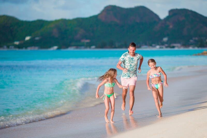 Pai feliz com jogo das crianças na praia Família feliz que tem o divertimento durante férias da praia do verão imagem de stock royalty free