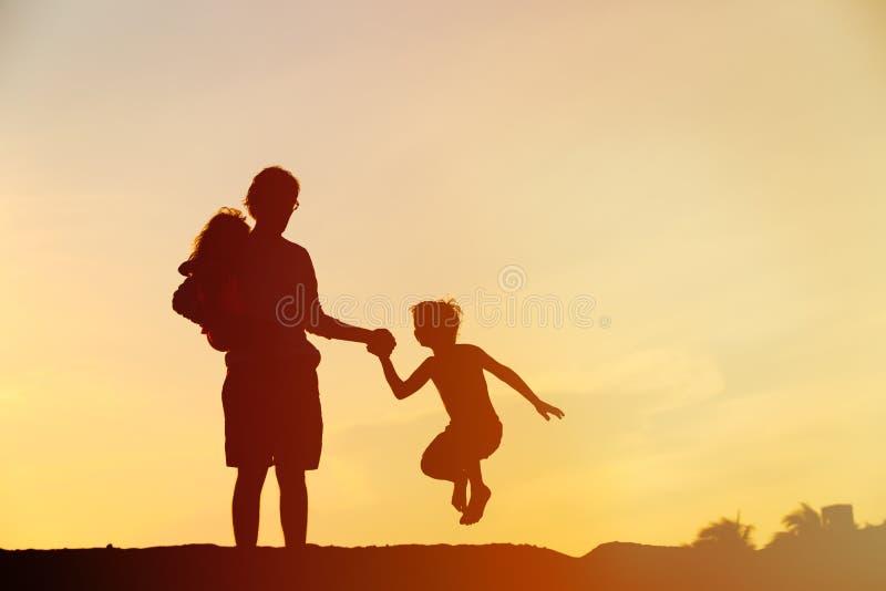 Pai feliz com o filho e a filha que saltam no por do sol fotografia de stock royalty free