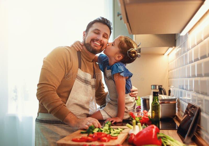 Pai feliz da família com a filha da criança que prepara a salada vegetal foto de stock