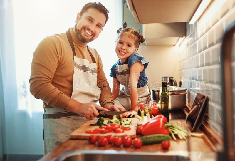 Pai feliz da família com a filha da criança que prepara a salada vegetal imagem de stock royalty free