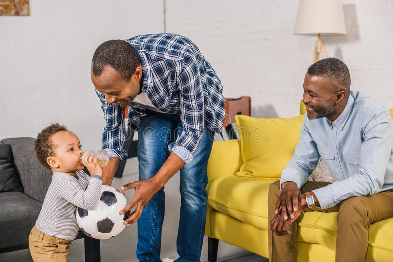 pai feliz e avô que olham a criança adorável que guarda a bola de futebol e que bebe da garrafa de bebê imagem de stock