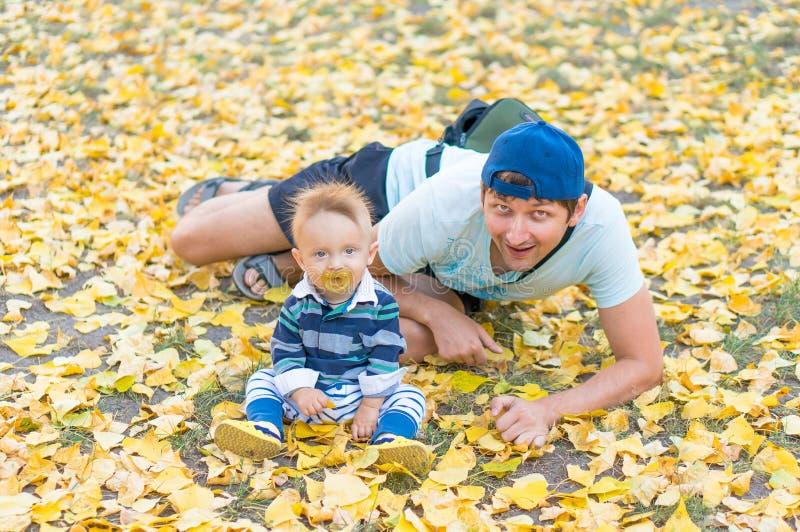 Pai feliz e bebê pequeno que jogam com outono das folhas do amarelo imagem de stock