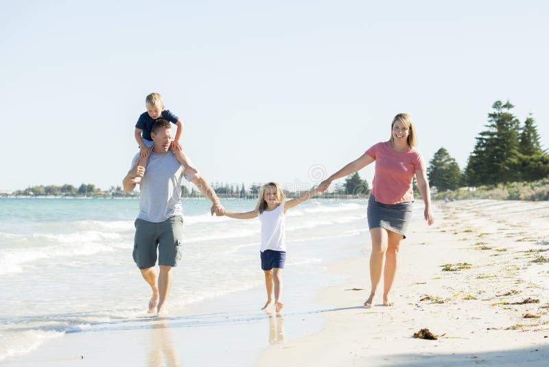Pai feliz e bonito novo da mãe da família que guarda a mão do passeio do filho e da filha alegre na praia que aprecia o holida do imagem de stock