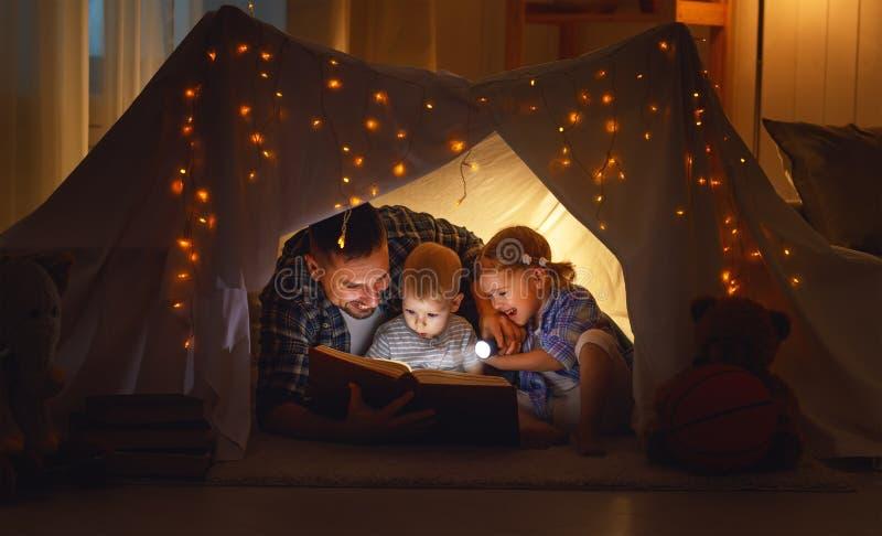 Pai feliz e crianças da família que leem um livro na barraca no hom fotos de stock