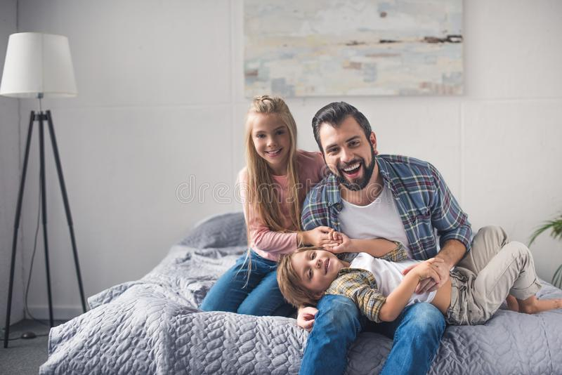 pai feliz e crianças que descansam na cama junto fotos de stock royalty free