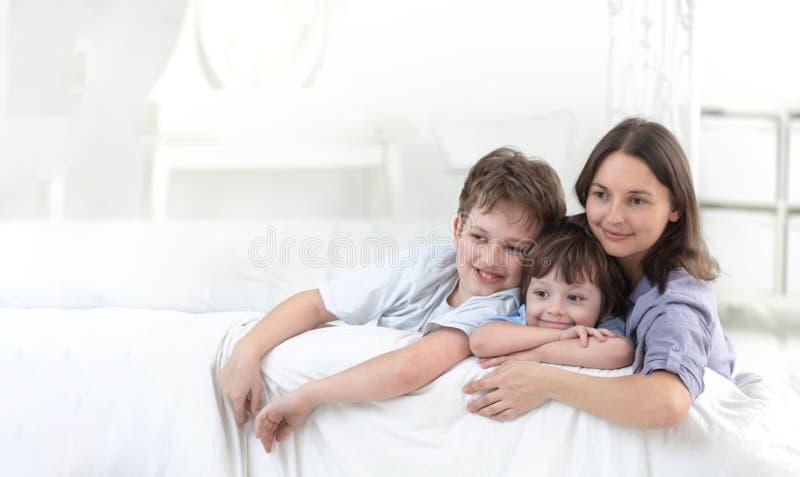 Pai feliz e crianças que têm o divertimento que senta-se junto no sofá fotos de stock