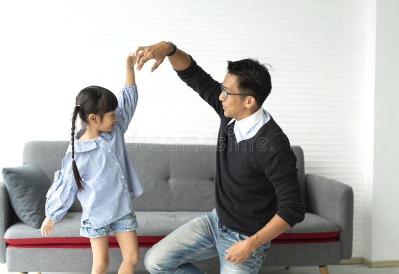 Pai feliz e filha asiáticos que jogam a dança junto na sala de visitas em casa fotos de stock