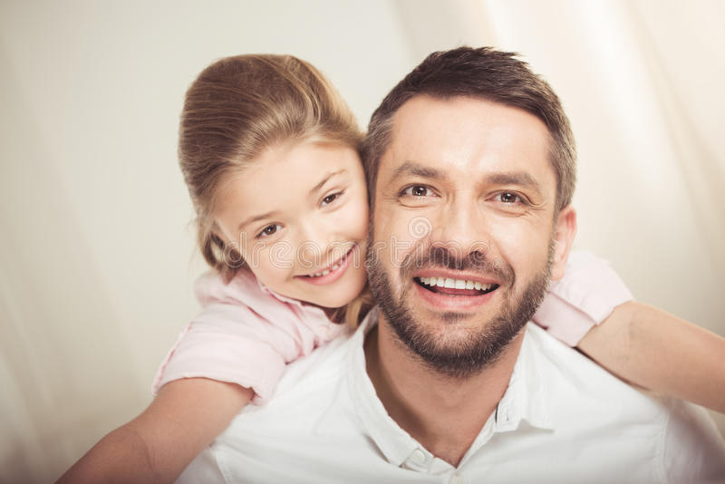Pai feliz e filha que abraçam e que sorriem na câmera fotografia de stock royalty free