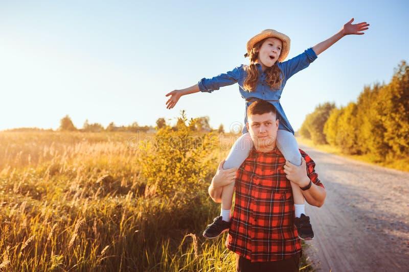 Pai feliz e filha que andam no prado do verão, tendo o divertimento e o jogo imagem de stock