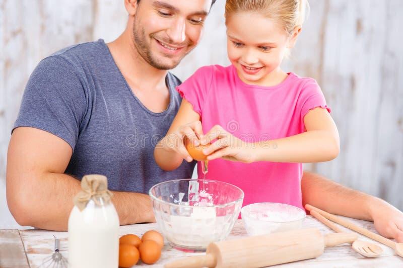 Pai feliz e filha que cozem junto foto de stock royalty free