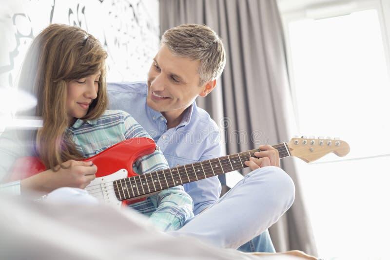 Pai feliz e filha que jogam a guitarra elétrica em casa foto de stock