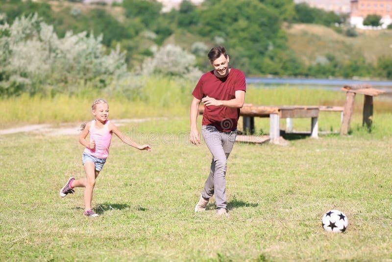 Pai feliz e filha que jogam o futebol fora foto de stock