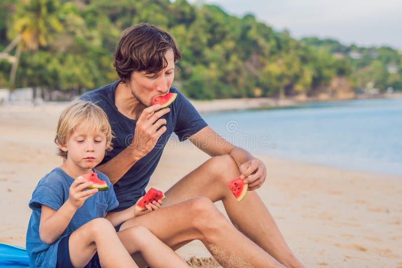 Pai feliz e filho da família que comem uma melancia na praia As crianças comem o alimento saudável imagem de stock royalty free