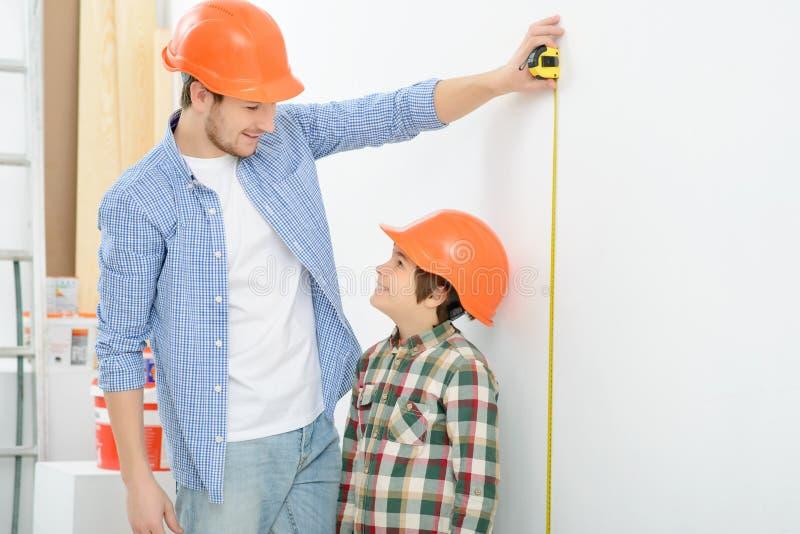 Pai feliz e filho que fazem a renovação imagem de stock royalty free
