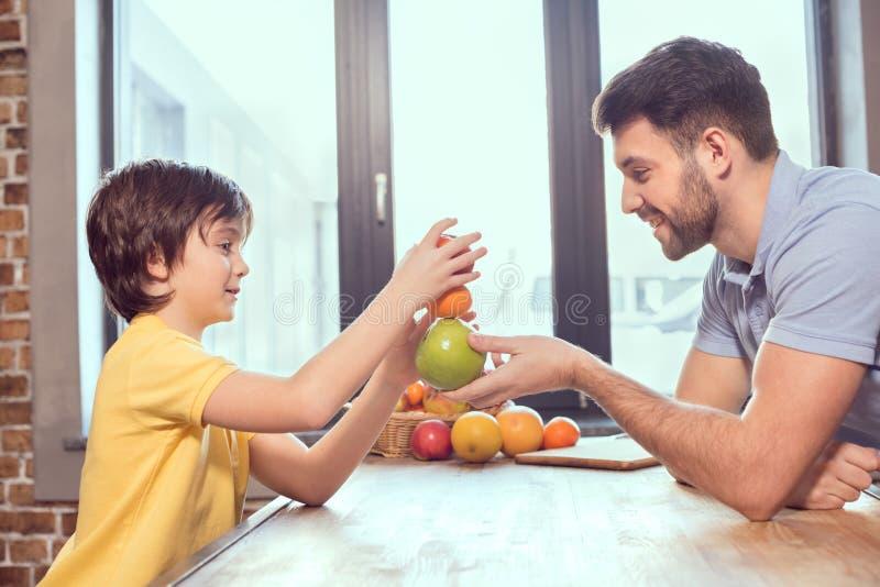 Pai feliz e filho que jogam com citrinas na cozinha imagem de stock royalty free