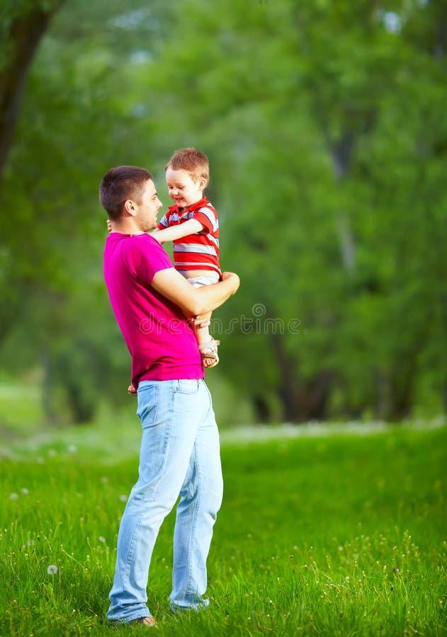 Pai feliz e filho que jogam na floresta da mola imagens de stock