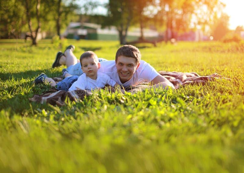 Pai feliz e filho que têm o divertimento que encontra-se na grama no verão imagens de stock