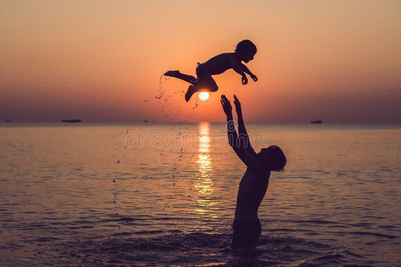 Pai feliz e filho que têm o tempo da família da qualidade na praia sobre foto de stock royalty free