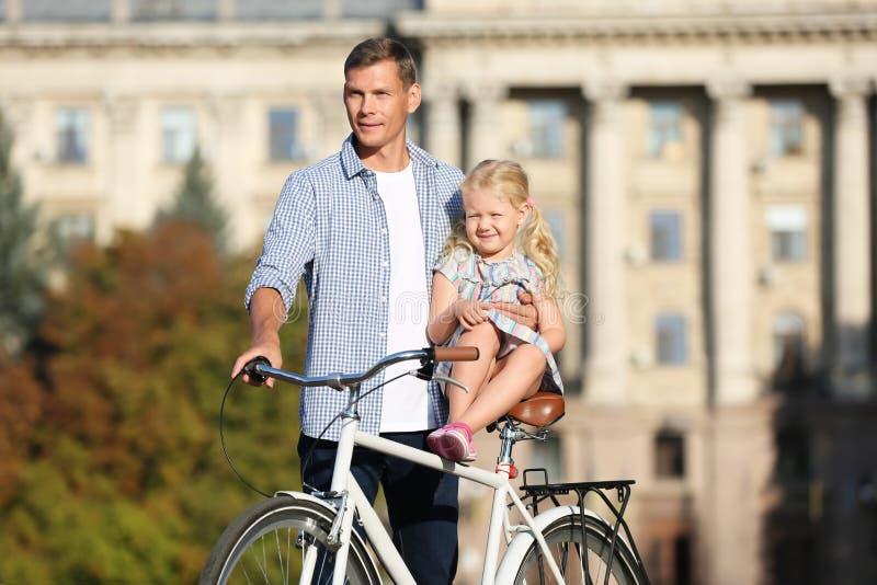 Pai feliz e sua filha com bicicleta fora imagens de stock