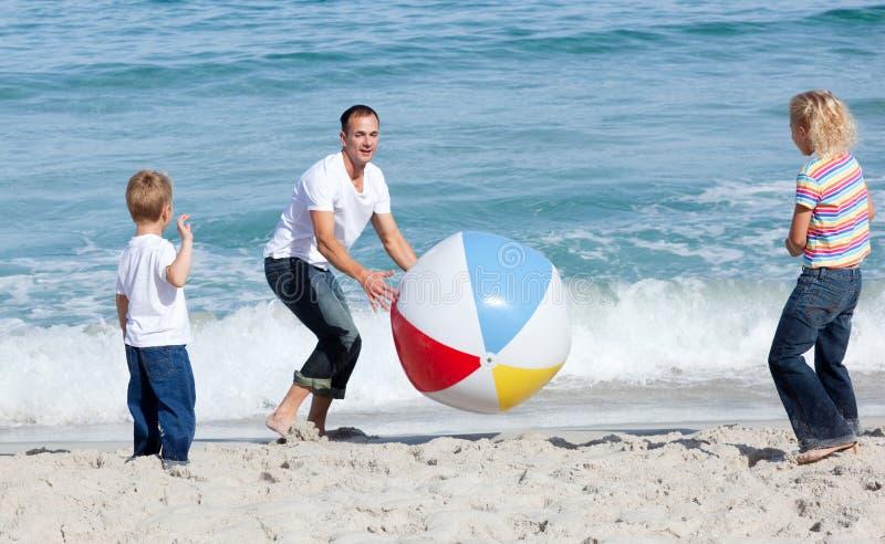 Pai feliz e suas crianças que jogam com uma esfera foto de stock