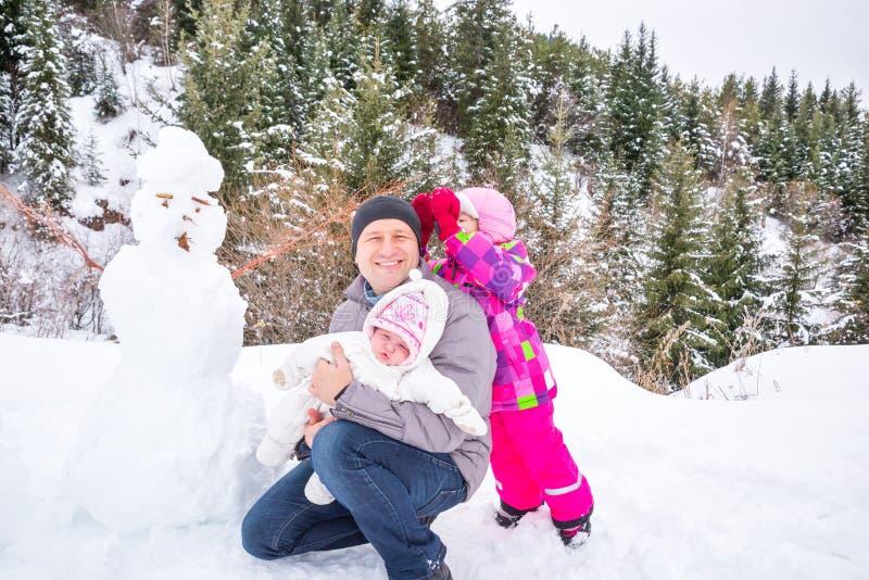 Pai feliz e suas duas filhas que constroem um boneco de neve no dia de inverno Família que joga na natureza com a floresta no fun fotos de stock