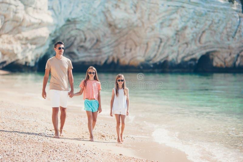 Pai feliz e suas filhas pequenas ador?veis na praia tropical que tem o divertimento fotos de stock royalty free