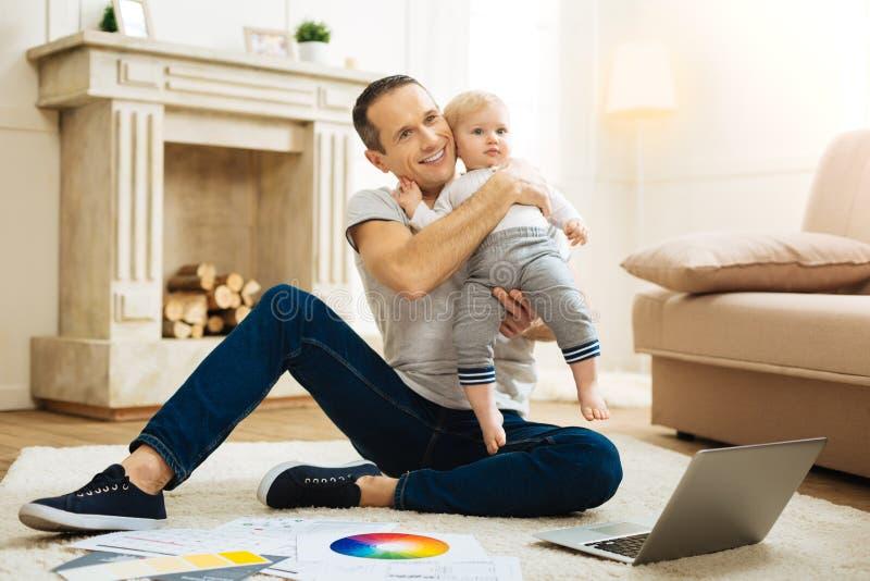 Pai feliz emocional que abraça sua criança ao sentar-se e ao trabalhar fotos de stock