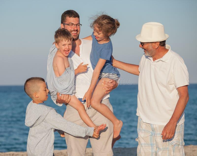 Pai feliz Kids Grandfather do mar da família das gerações foto de stock