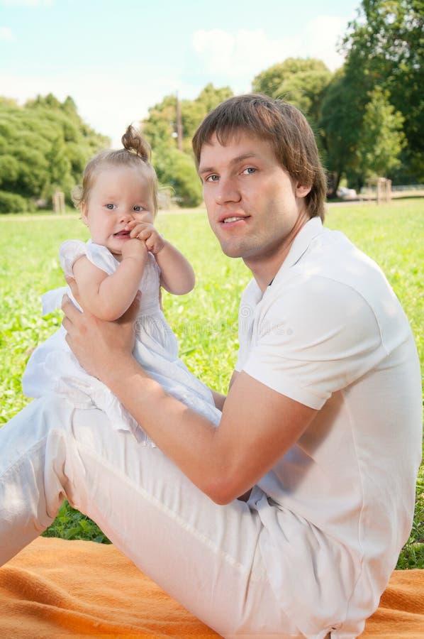 Pai feliz novo com a filha no parque imagens de stock royalty free