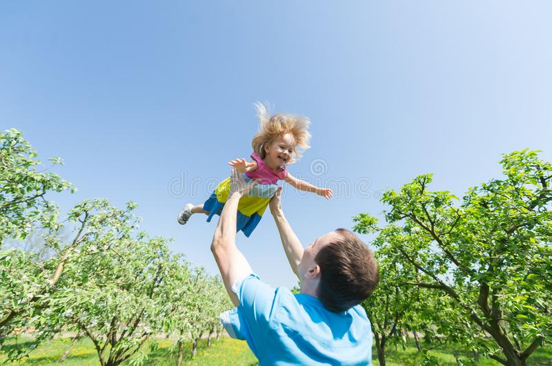 Pai feliz novo que sustenta sua filha no ar contra o céu fotografia de stock