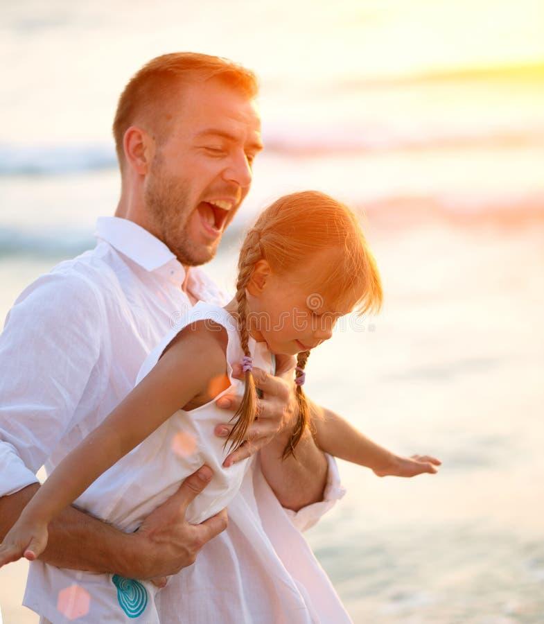 Pai feliz novo que tem o divertimento com sua filha pequena imagem de stock
