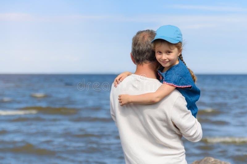 Pai feliz que abraçam sua pouca filha na praia, pai e filha que andam na praia e que levantam à câmera fotografia de stock royalty free