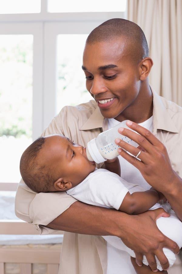 Pai feliz que alimenta a seu bebê uma garrafa fotos de stock