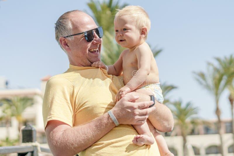 Pai feliz que guarda o filho alegre durante f?rias tropicais foto de stock royalty free