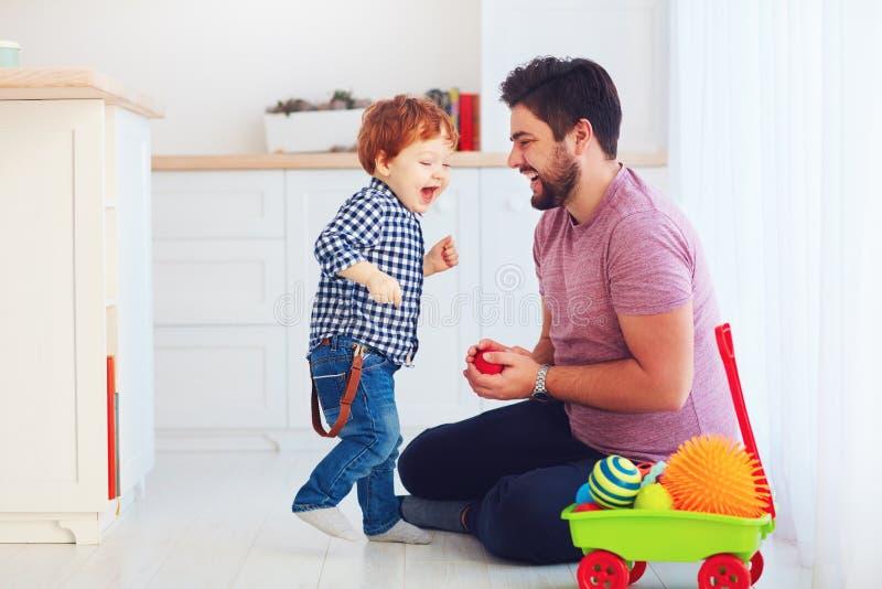 Pai feliz que joga com o filho bonito do bebê da criança em casa, jogos da família imagens de stock royalty free