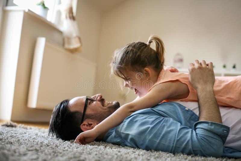 Pai feliz que joga em casa com sua filha imagem de stock royalty free