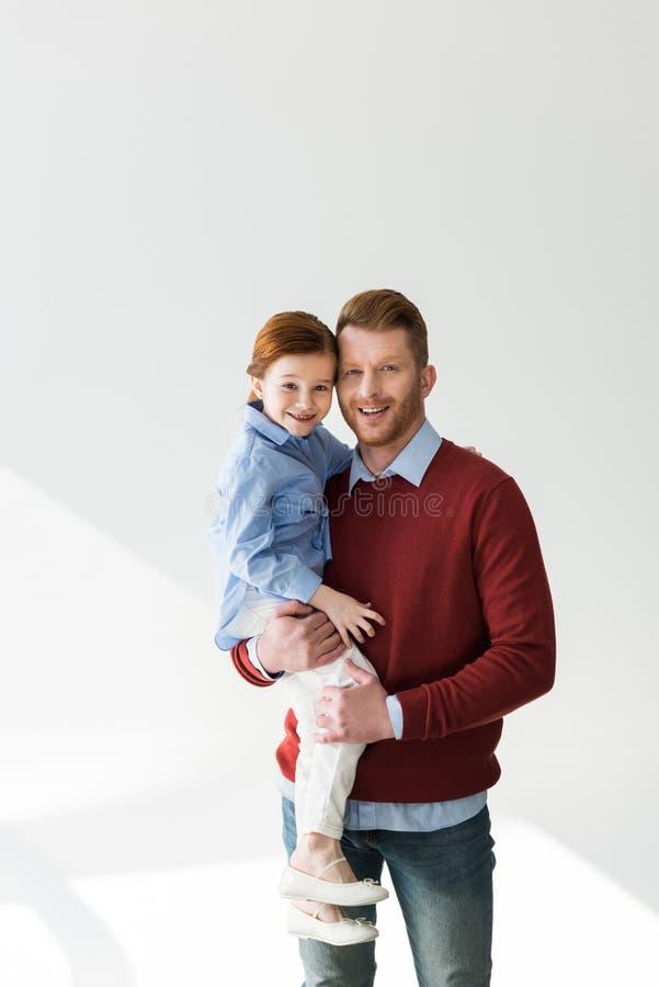 Pai feliz que leva a filha pequena adorável e que sorri na câmera fotos de stock royalty free