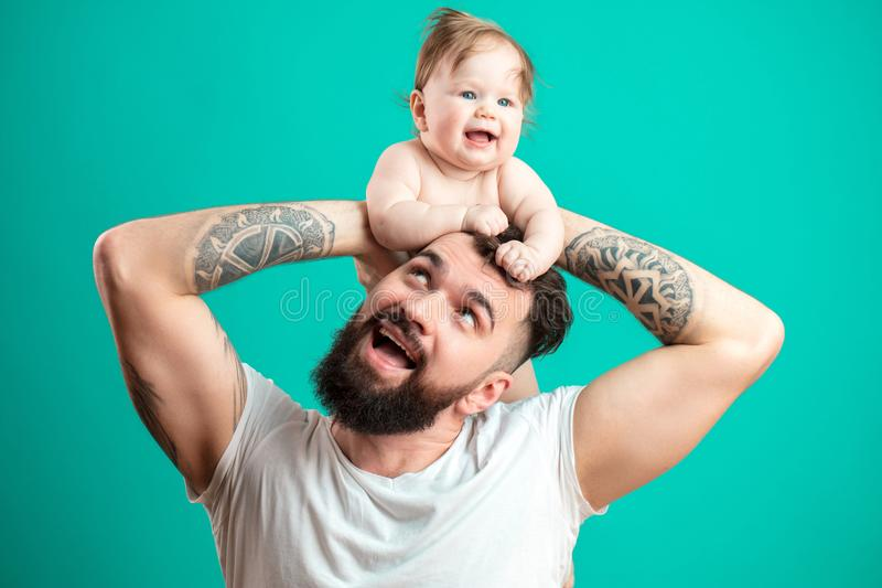 Pai feliz que leva sua filha infantil no pescoço isolado sobre o fundo azul imagem de stock royalty free
