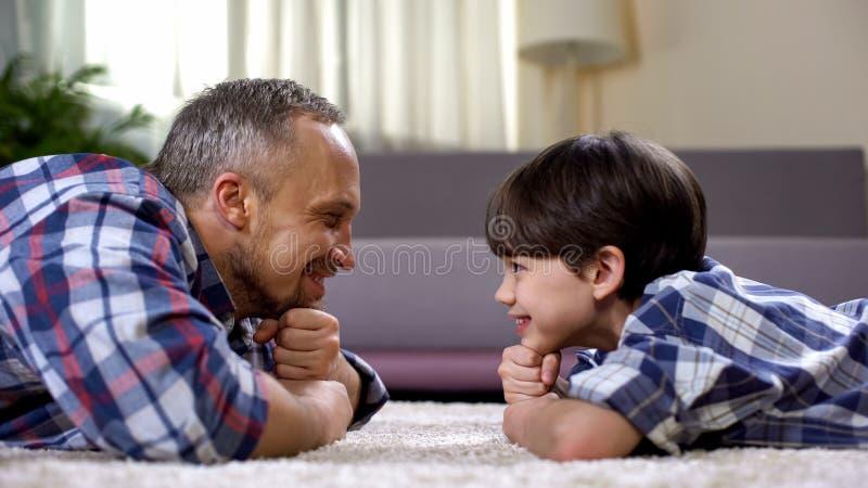 Pai feliz que olha o filho, passando o tempo junto no fim de semana, paternidade fotos de stock royalty free
