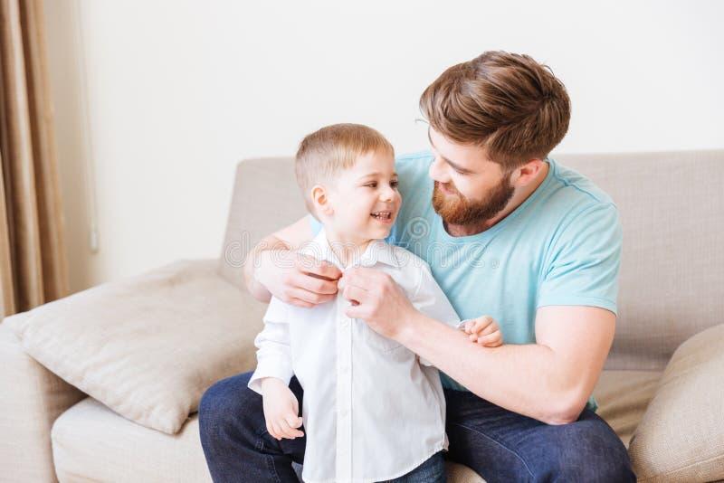 Pai feliz que senta-se no sofá e que veste seu filho pequeno imagens de stock